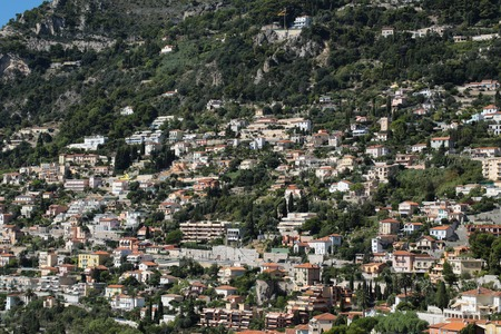 populated: Monte Carlo, Monaco - September 20, 2015: view of mountain with densely populated city with residential buildings green trees on cityscape background, horizontal picture Editorial