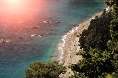shingle beach: beautiful seaside seen from above shingle beach line blue sea and green trees water-based leisure area sun spot on coastline background, horizontal picture
