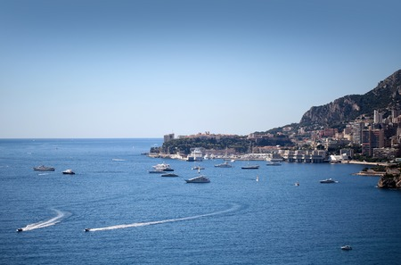 day time: Monte Carlo, Monaco - September 20, 2015: city coastline sea beach residential buildings against high mountains day time blue sky on seascape background, horizontal picture