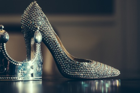 Female sprakling glamour luxury shoe on high heel and silver crown on reflecting table top close, glamour fashion concept, horizontal picture Archivio Fotografico