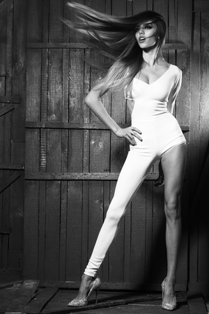 catsuit: Sexy fashionable young pretty woman with windy long hair slim legs and straight body in white glamour catsuit on wooden background, vertical picture Stock Photo