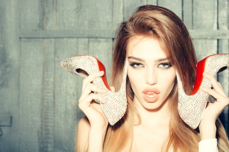 glamour hair: Portrait of sexy glamour fashion young girl with long beautiful hair holding shoes in hands near face with tongue on wooden background, horizontal picture