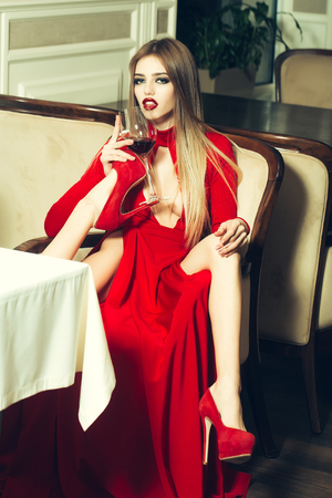 Glamour sexy flexible young woman with long blonde hair sitting in restaurant holding wine glass in elegant red dress and shoes with straight raised legs, vertical picture