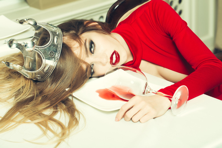 Sensual elegant glamour young drunk woman with beautiful hair in silver crown lying on table with glass and poored red wine in plate after hangover, horizontal picture