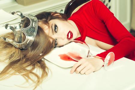 Sensuele elegante glamour jonge dronken vrouw met mooie haren in zilveren kroon liggend op tafel met glas en poored rode wijn in de plaat na de kater, horizontaal beeld