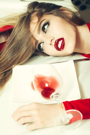 drunk woman: Sensual elegant glamour young drunk woman with beautiful hair lying on table with glass and poored red wine in plate after hangover, vertical picture