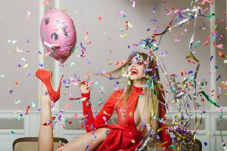 Happy emotional glamour smiling young woman with long hair straight body and slim legs in red dress and shoes with birthday holiday ballon on heel and confetti sitting on table, horizontal photo