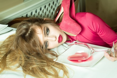 drunk woman: Sensual elegant glamour young drunk woman with beautiful hair lying on table with glass and poored red wine in plate after hangover with suide shoe, horizontal picture