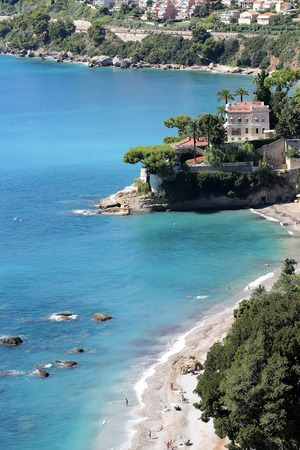 shingle beach: Monte Carlo, Monaco - September 20, 2015: beautiful white villa seen from above shingle beach line blue sea and green trees water-based leisure area on coastline background, vertical picture Editorial