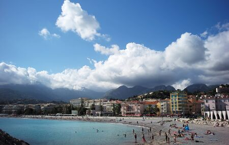 menton: MENTON, FRANCE - September 19, 2015: Beach on shores of azure sea in Menton with hotels against mountains covered with clouds, horizontal photo