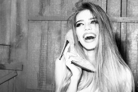木製の背景、画像の水平方向の携帯電話としての顔近く手に靴を保持長く美しい髪と幸せの笑みを浮かべてグラマー ファッション若い女の子の肖像