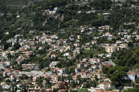 populated: Monte Carlo, Monaco - September 20, 2015: view of mountain with densely populated city with residential buildings green trees on cityscape background, horizontal picture Stock Photo