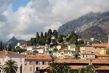 mount saint michael: Menton. France - Month09.2015: Delightful panorama of french urban view of popular resort surrounded by green trees on amazing mountain covered white clouds background outdoor, horizontal picture