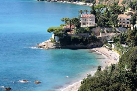 shingle beach: Monte Carlo, Monaco - September 20, 2015: beautiful white villa seen from above shingle beach line blue sea and green trees water-based leisure area on coastline background, horizontal picture Stock Photo