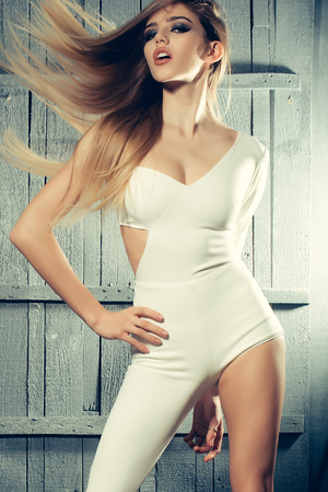 catsuit: Sexy fashionable young pretty woman with windy long hair and straight body in white catsuit on wooden background, vertical picture Stock Photo