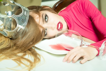 sexual girl: Sensual elegant glamour young drunk woman with beautiful hair in silver crown lying on table with glass and poored red wine in plate after hangover, horizontal picture