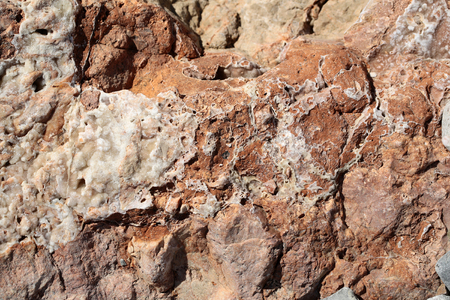 costal: Photo closeup of costal beach sharp brown terracotta rock stone formations covered with salt minerals solid layer on natural background, horizontal picture