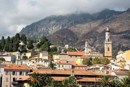 the place is outdoor: Wonderful urban sight of famous resort in french reviera historical place buildings with brick roofs standing opposite alps mountains outdoor, horizontal pciture