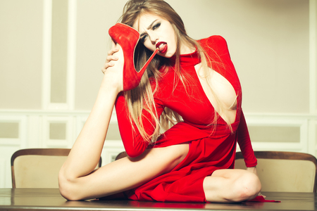 Sexy fashionable glamour young woman with long hair straight body and slim legs in red dress and shoes licking heel sitting on table indoor, horizontal picture