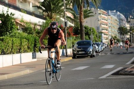 thumbsup: Menton, Roquebrune Cap Martin, France - September 20, 2015:  one rider in helmet gives thumbs-up competes in duathlon bicycle racing on paved roads on streetscape background, horizontal picture Editorial
