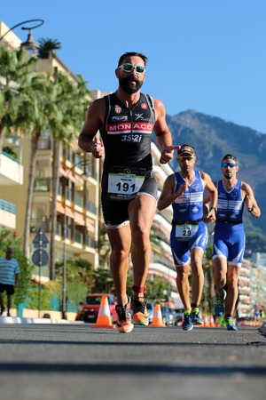 thumbsup: Menton, Roquebrune Cap Martin, France - September 20, 2015: first runner gives thumbs-up during duathlon event team running cross city on paved roads on streetscape background, vertical picture Editorial