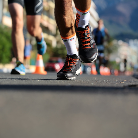 Menton, Roquebrune Cap Martin, France - September 20, 2015: legs of runners from different teams compete in duathlon running cross city on paved roads on streetscape background, square picture