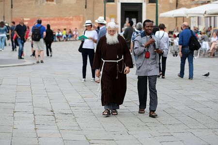 priesthood: VENICE, ITALY - SEPTEMBER 22: Unidentified priest with grey beard in brown robe with african man walking and speaking along famous venetian square with crowd of tourists outdoor, horizontal picture