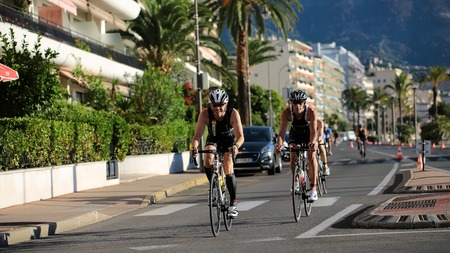 smilies: Menton, Roquebrune Cap Martin, France - September 20, 2015:  one rider first ahead smilies and competes in duathlon bicycle racing on paved roads on streetscape background, horizontal picture