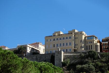 town houses: Monte Carlo, Monaco - September 20, 2015: town houses stand on mountain top protected by defensive wall and half moon day time view from bottom on bright blue sky background, horizontal picture Editorial