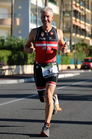 thumbsup: Menton, Roquebrune Cap Martin, France - September 20, 2015: one runner ahead gives thumbs-up competes in duathlon running cross city on paved roads on streetscape background, vertical picture