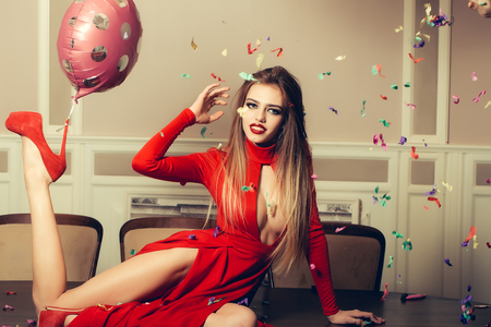 chads: Happy emotional glamour smiling young woman with long hair straight body and slim legs in red dress and shoes with birthday holiday ballon on heel and confetti sitting on table, horizontal photo