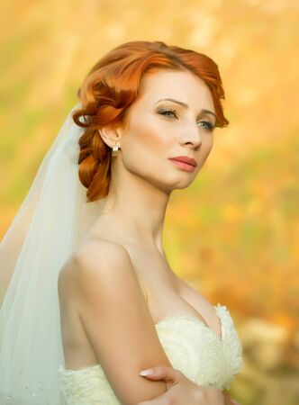Portrait of thoughtful sensual elegant red haired bride woman in white wedding dress looking away outdoor on blurred yellow background, vertical picture