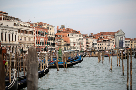 the place is outdoor: VENICE, ITALY - SEPTEMBER 22: Delightful cityscape of many gondolas ashore pier along venetian beautiful street with vintage  colorful houses near Londra palace historical place outdoor, horizontal