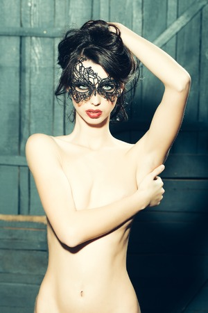 sexy nackte frau: Attractive mysterious sexy young sensual woman with brunette hair in lace black mask looking forward standing topless with hand on bare chest in studio on wooden background, vertical picture