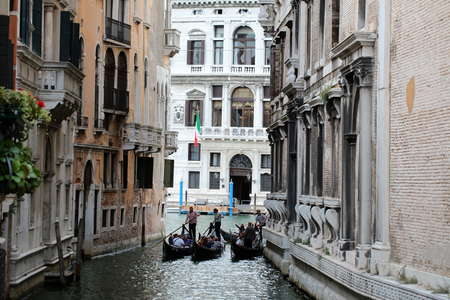 sculling: VENICE, ITALY - SEPTEMBER 22: Three splendid gondola sculling on delightful romantic authentic pure venetian narrow old street with amazing historical vintage buildings outdoor, horizontal picture