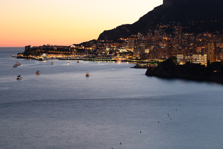 seascape: Monte Carlo, Monaco - September 20, 2015: night view of city at bottom of mountain sea port harbor shore yachts beautiful illumination against clear dusk sky on seascape background, horizontal picture Stock Photo