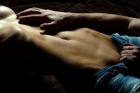 black girl nude: Male hand undressing young sensual woman with bare belly in torn blue sexy jeans lying in studio on dark background closeup, horizontal picture