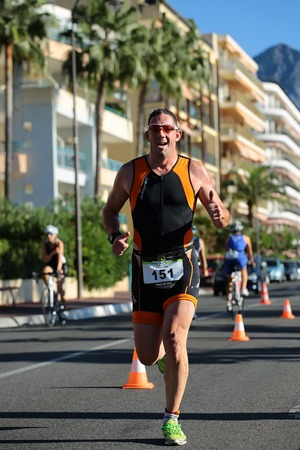 thumbsup: Menton, Roquebrune Cap Martin, France - September 20, 2015: runner ahead in sunglasses gives thumbs-up competes in duathlon running cross city paved roads on streetscape background, vertical picture Editorial
