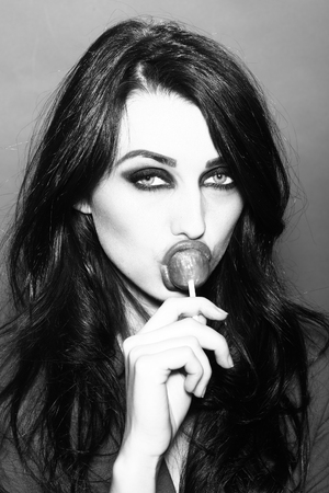 portarit: Portarit of glamour sexy young woman with long lush brunette hair eating and licking sweet lollipop on stick on studio background black and white, vertical picture Stock Photo