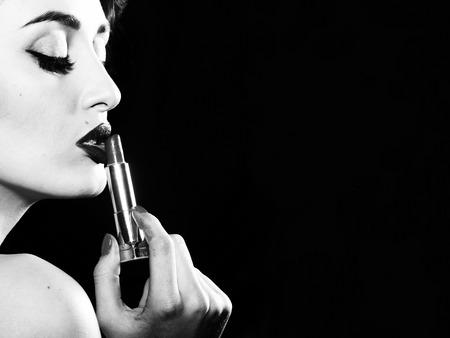 Retrato de la atractiva sensual encanto retro elegante mujer reflexiva joven adulta con el peinado clásico y los labios rojos sosteniendo el lápiz labial en el vestir en el fondo negro espacio de la copia, cuadro horizontal
