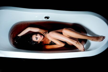 Attractive sexy young adult sensual woman with wet brunette woman lying in dress in dark water in white bath tub with long straight legs indoor in studio on black background, horizontal picture