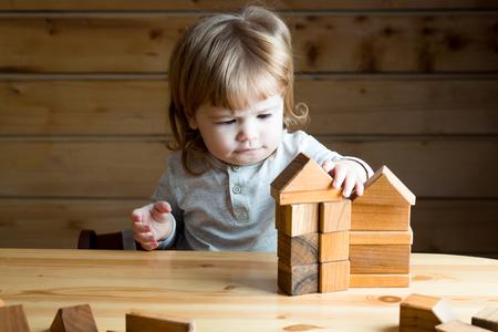 Carino ragazzo concentrato concentrato con lunghi capelli ricci biondi giocando e costruendo casa giocattolo da blocchi di legno interni, immagine orizzontale Archivio Fotografico