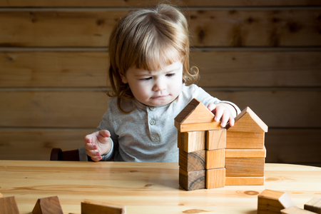 Cute concentrated small baby boy with long blonde curly hair playing and building toy house from wooden blocks indoor, horizontal picture