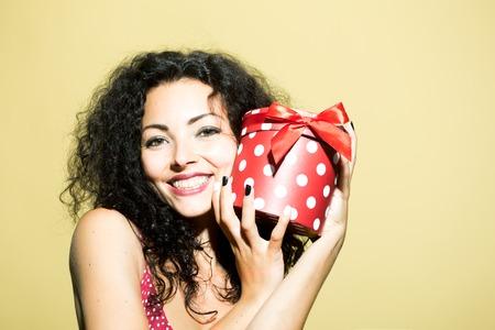 Belle heureuse émotionnelle souriante jeune femme brune adulte avec de longs cheveux bouclés en robe rouge présente boîte intérieure en studio sur fond jaune de vacances, de l'image horizontale