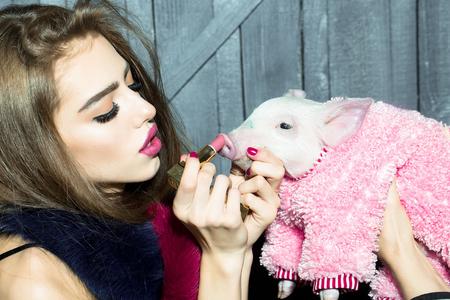 布と木の背景、画像の水平方向に手で口紅の美しい若い官能的なファッショナブルな女性持株かわいいピンク小豚ペット 写真素材