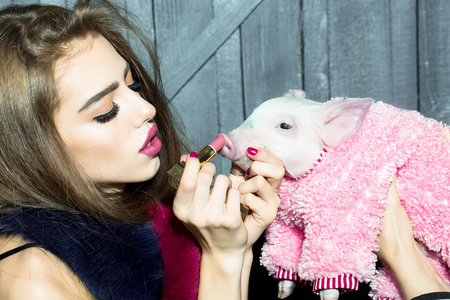 Beautiful young sensual fashionable woman holding cute pink small pig pet in cloth and lipstick in hands on wooden background, horizontal picture Stock Photo - 53660375