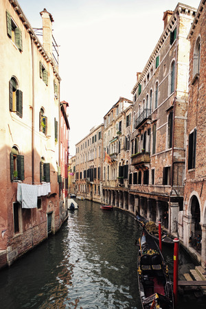 townscape: Venice, Italy - September 22, 2015: venetian canal narrow street between old aged residential buildings with black gondola at mooring in sea lagoon on townscape background, vertical picture