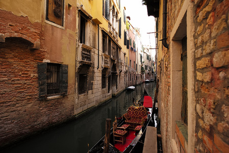 townscape: Venice, Italy - September 22, 2015: gondola traditional flat-bottomed venetian rowing boat black at mooring in narrow sea canal next to residential building on townscape background, horizontal picture Editorial