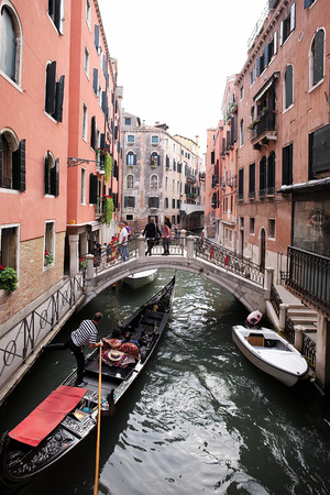 townscape: Venice, Italy - September 22, 2015: gondola with tourists propelled by gondolier who stands and rows along shallow venetian canal under bridge with people on townscape background, vertical picture