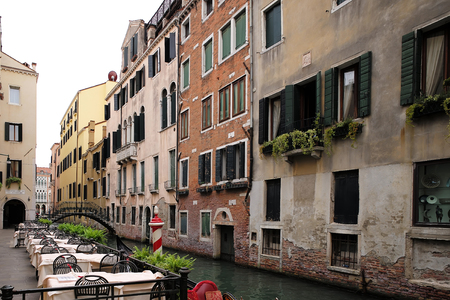 tall buildings: Venice, Italy - September 22, 2015: empty romantic restaurant faces aged tall buildings in open air by venetian canal with bridge on townscape background, horizontal picture Editorial